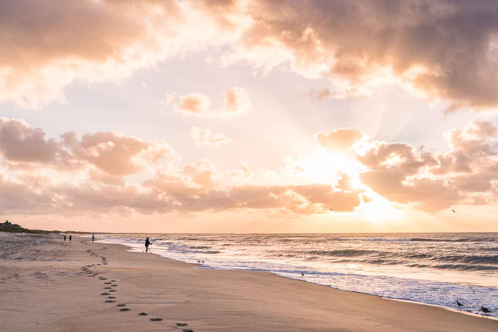 Landscape photography image of a fisherman on beach at sunrise