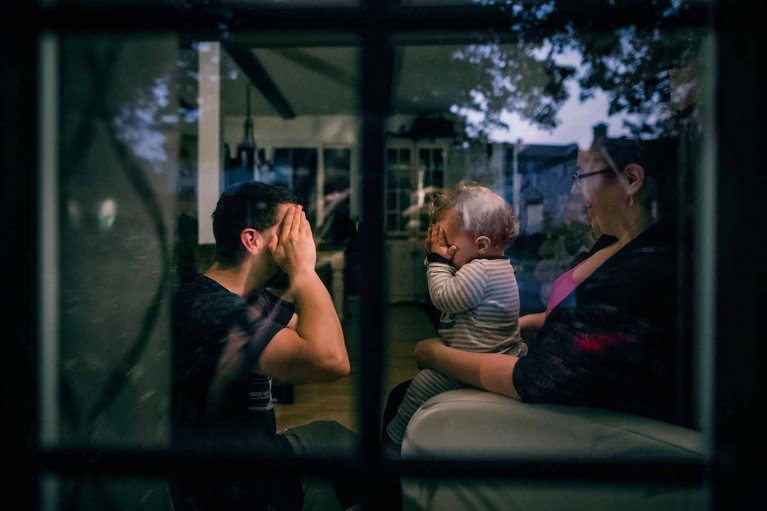 Family plays peek-a-boo, shot with creative composition through a window looking in