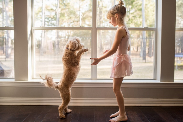 A girl in a ballet leotard plays with her dog in front of a big window