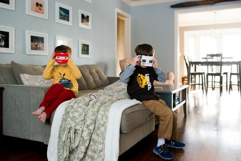 Two boys sit on a sofa and look through view finders