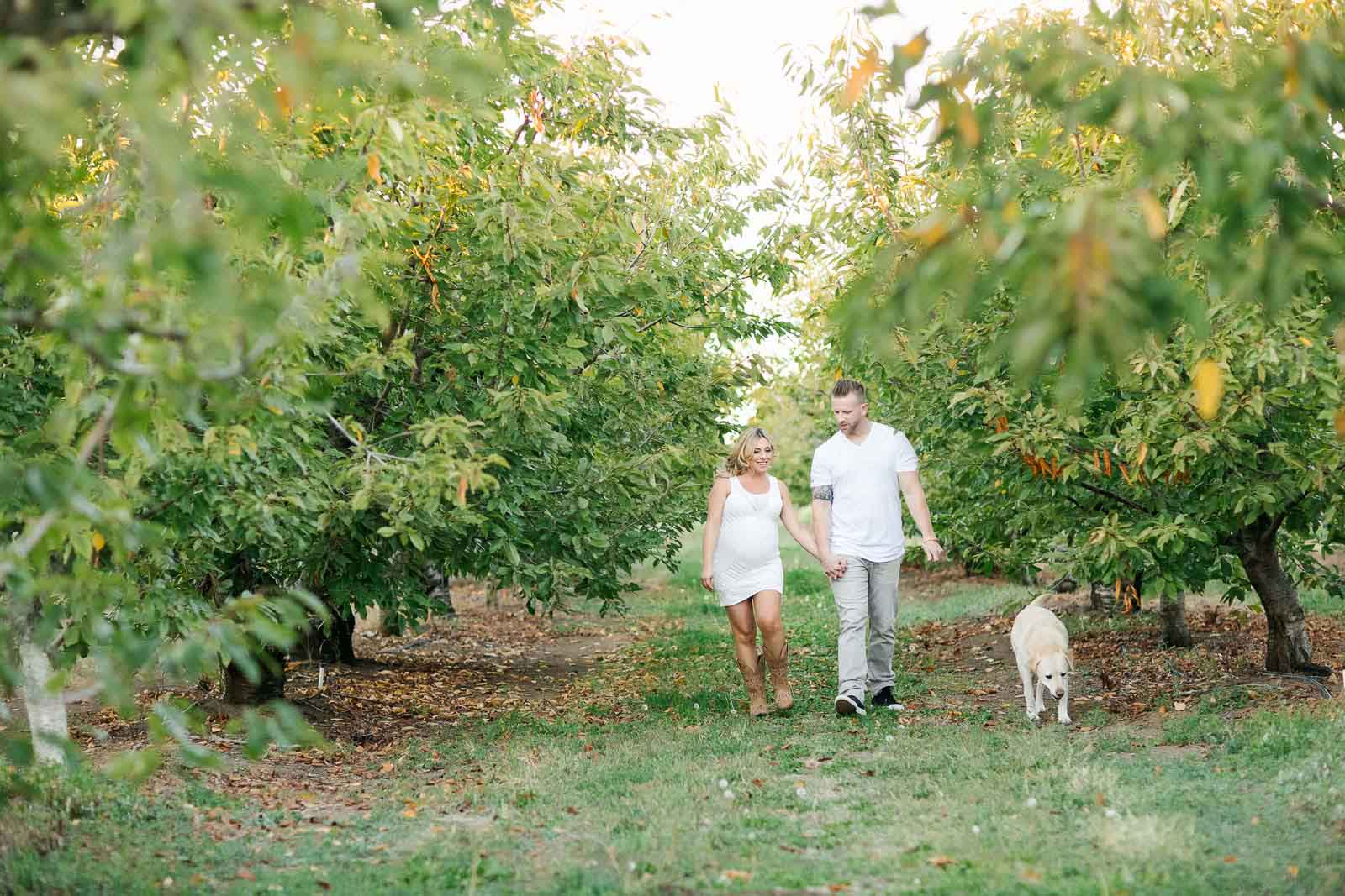 A couple walks through an orchard in Brentwood California