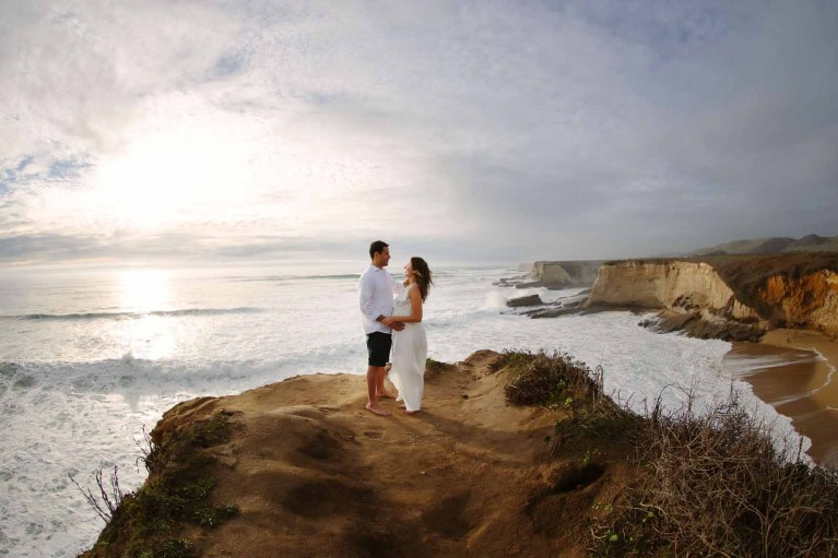 Travel session photo of a couple standing on a cliff taken in Davenport California