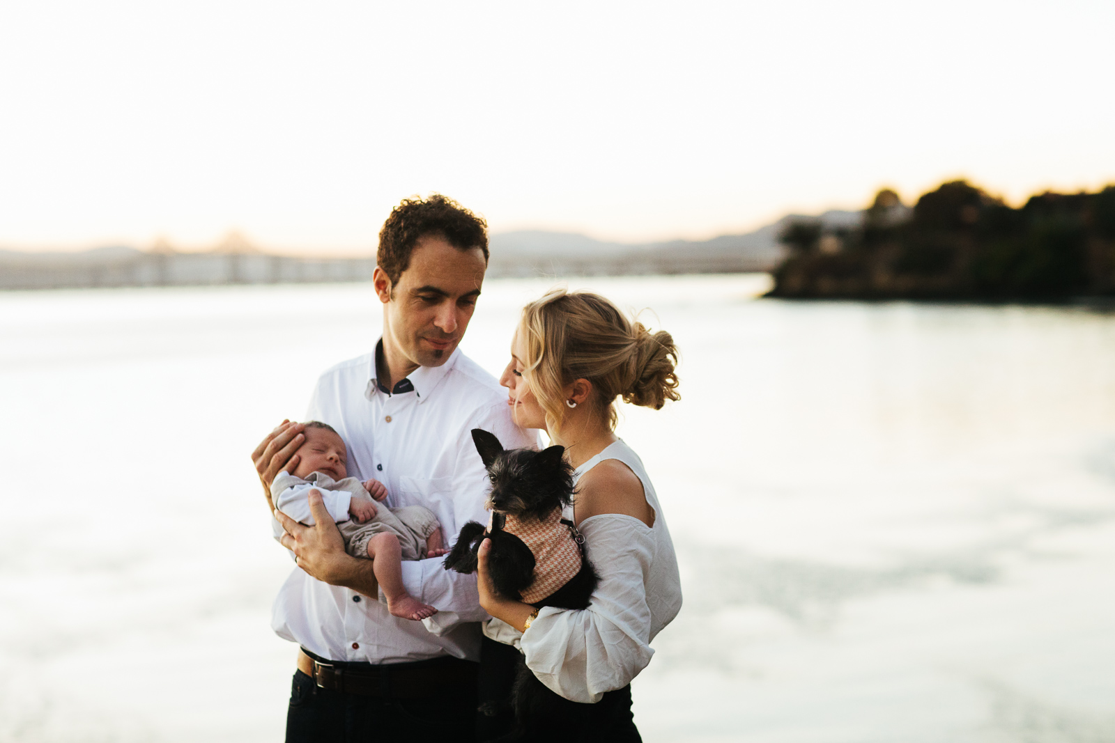Travel photo of a couple holding a newborn and a dog in Point Richmond, California