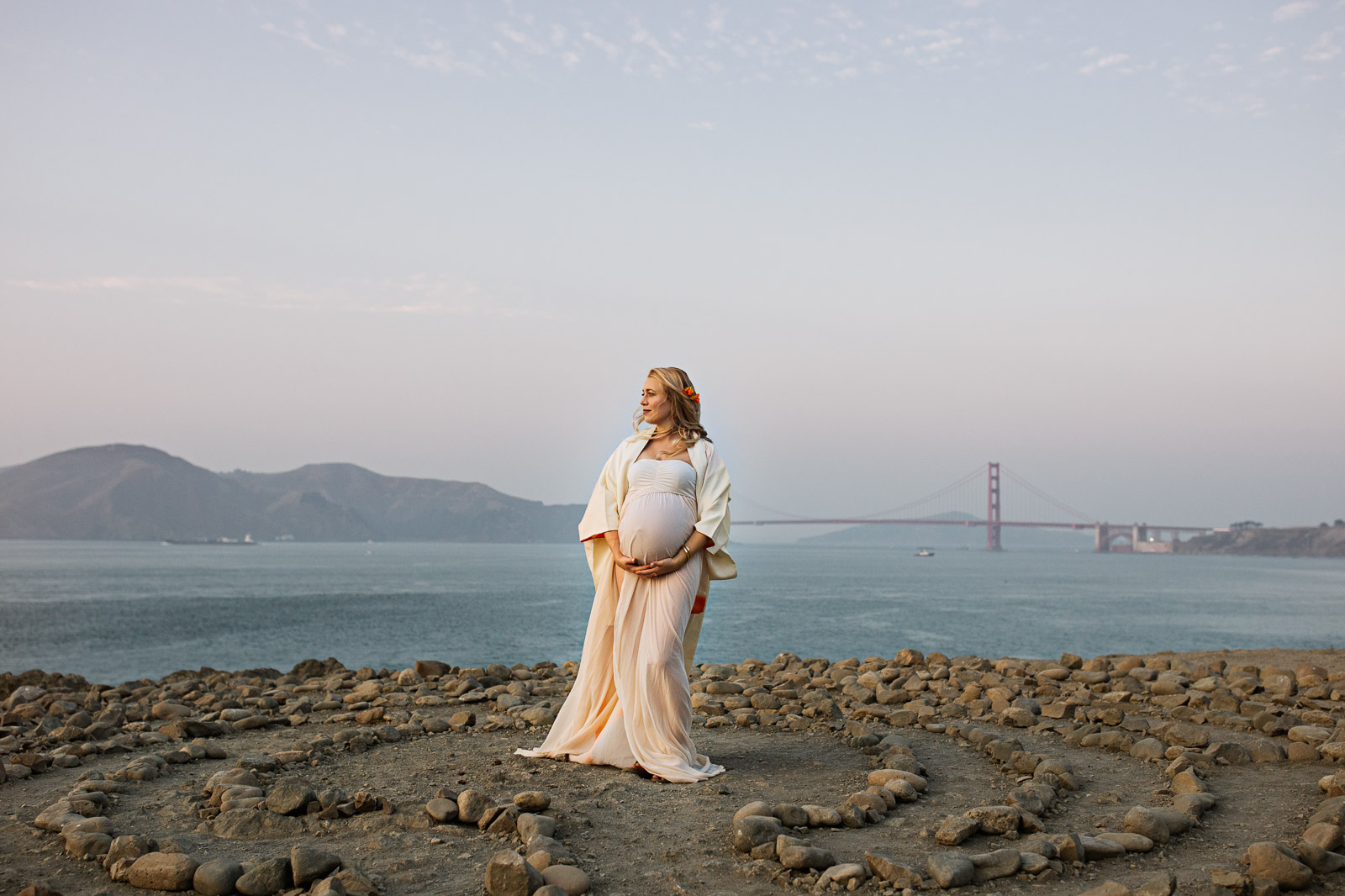 pregnant woman stands in front of the Golden Gate bridge