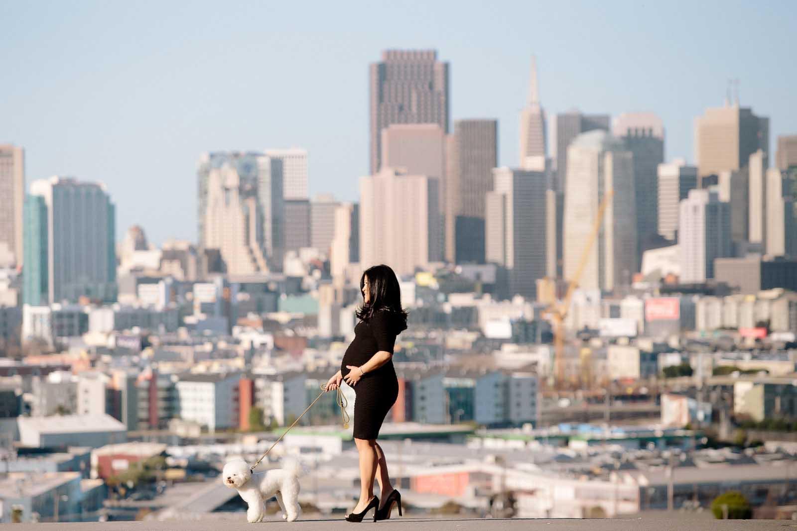 A pregnant woman walks a dog in font of San Francisco skyline