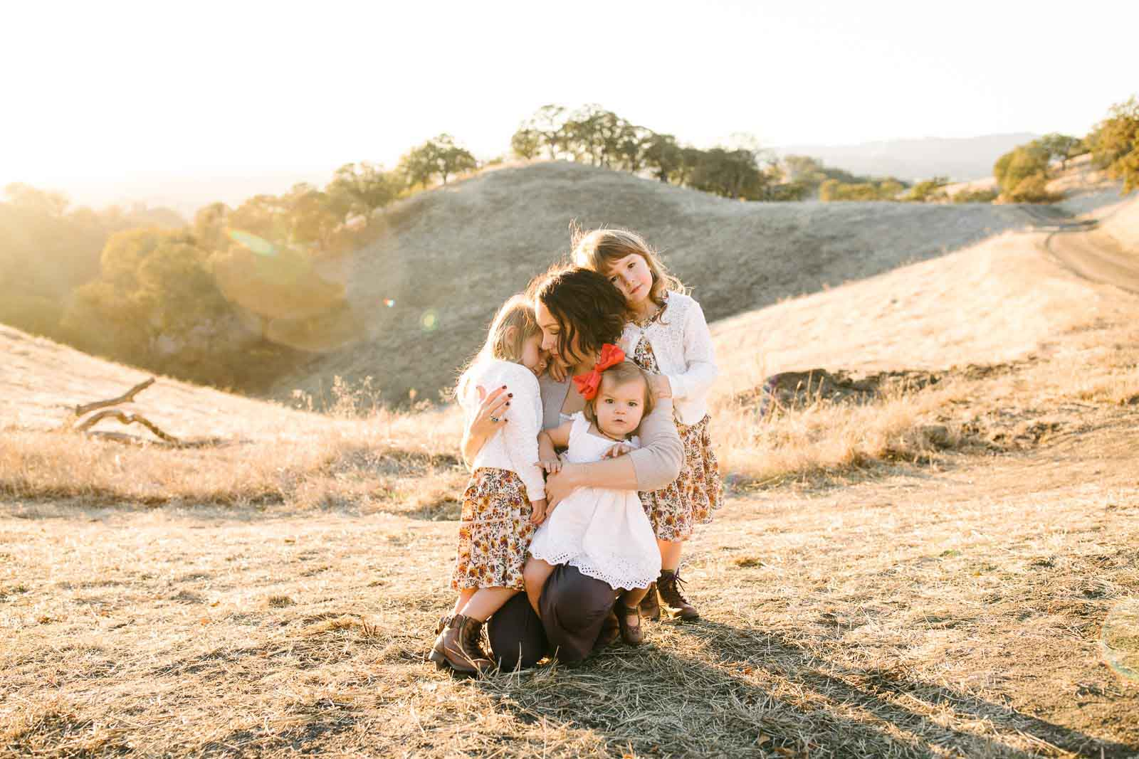 A photography travel session in Walnut Creek, a mom hugs her three girls