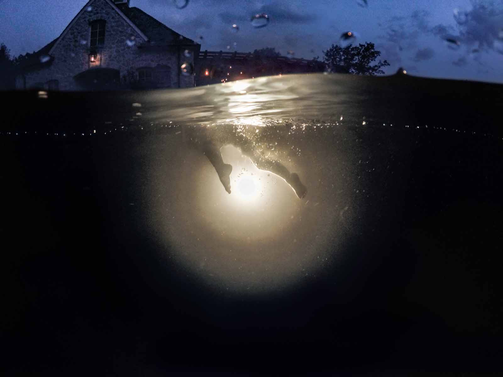 A little boy's legs in front of a light in an underwater photography session