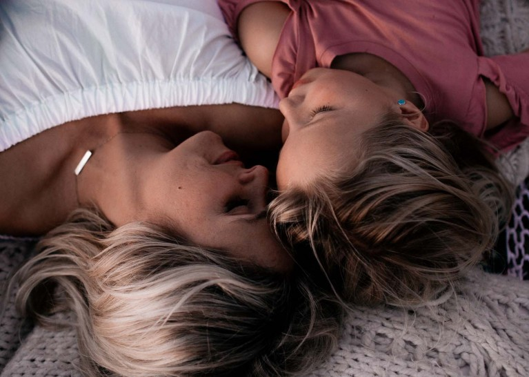 Emotional connection in photos through closed eyes, mom and daughter lay side by side