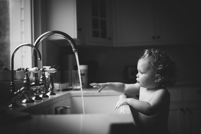 Girl reaching for water at a sink, by Melissa Gibson