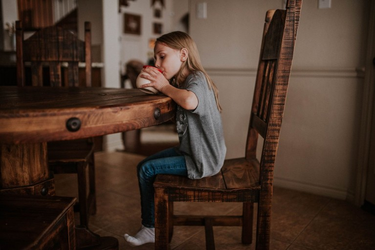 Girl drinks from a bowl at a wooden table at home