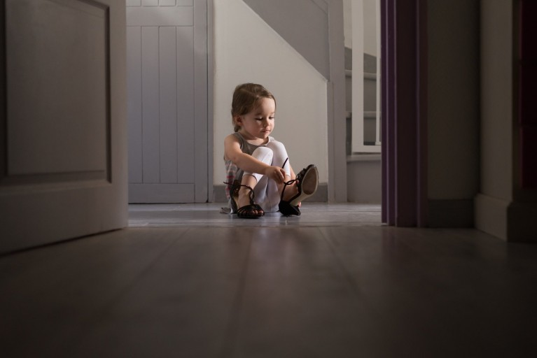 girl puts on moms heels in a patch of light at home
