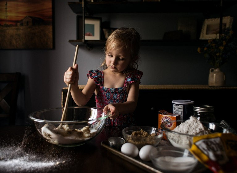 Girl stirs ingredients in a mixing bowl by Kate Luber