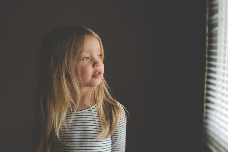 Photo of little girl looking out window in a favorite photography spot at home by Tiffany Kelly