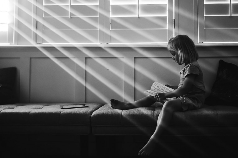 Girl sits reading on a window bench in dramatic sun rays by Cami Turpin