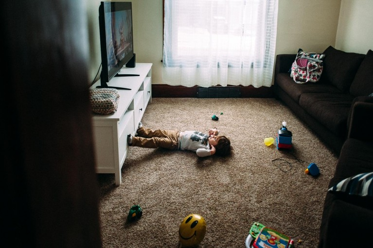Boy lays on ground in front of TV at home