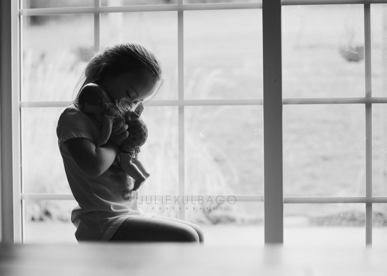 Little girl near window hugging a doll at home