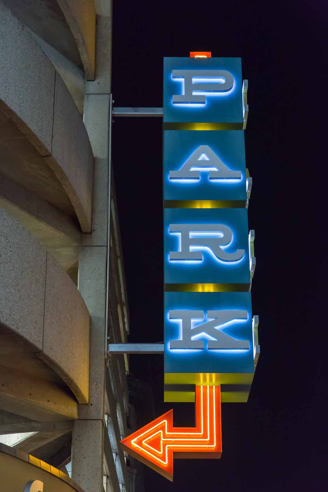 City lights at night, a sign says park