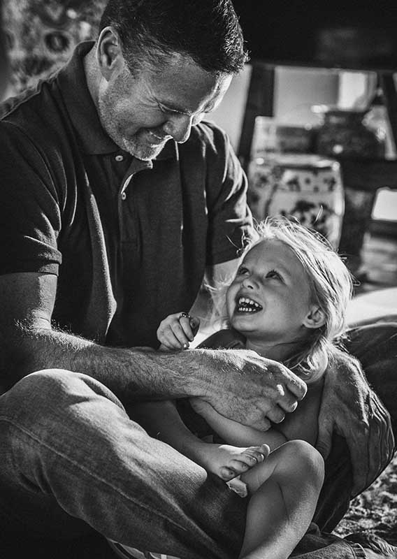 A father looks at his laughing daughter, showing unconditional love