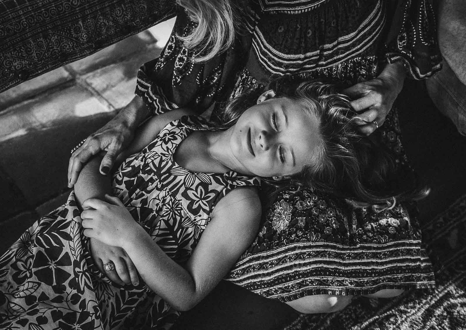A mother strokes her smiling daughter's hair, showing unconditional love