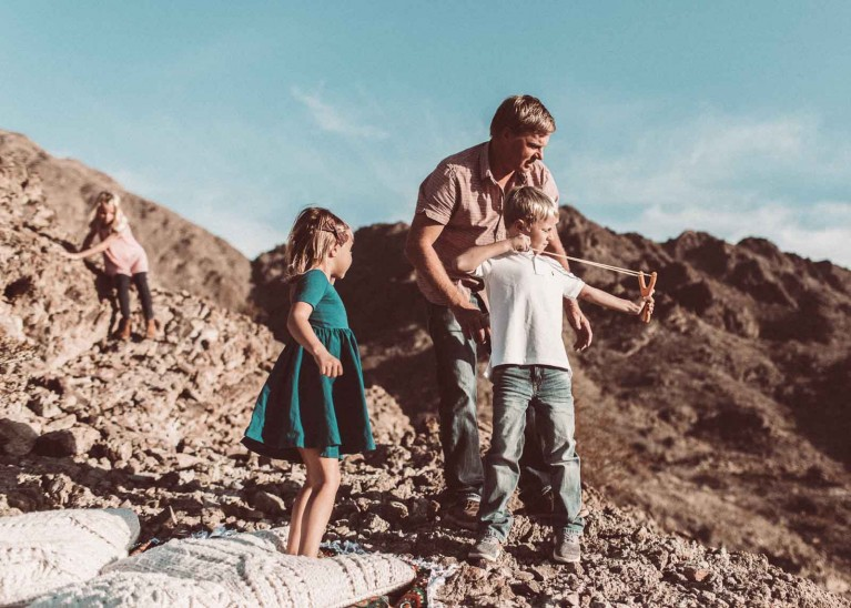 a father helps his son set up a sling-shot on a mountain