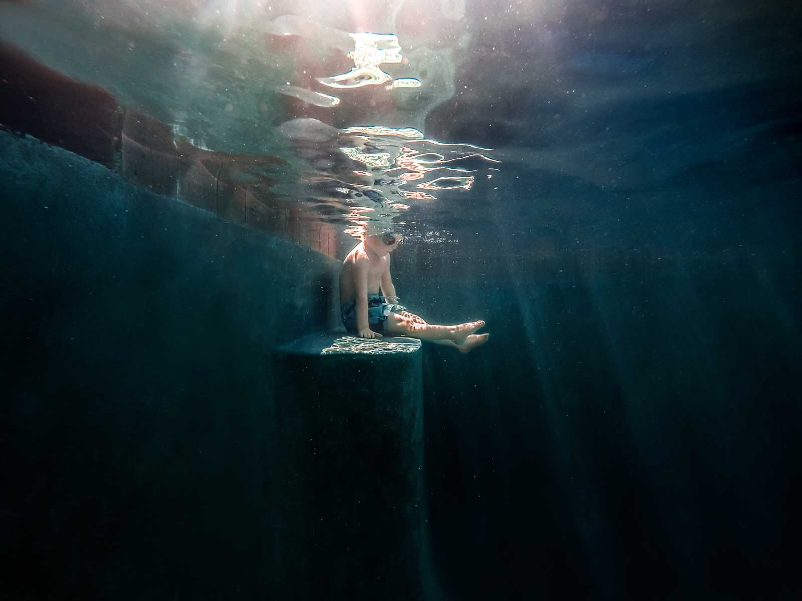 underwater photography edit of boy sitting in pool