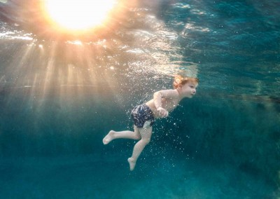 Underwater photography of boy swimming in pool