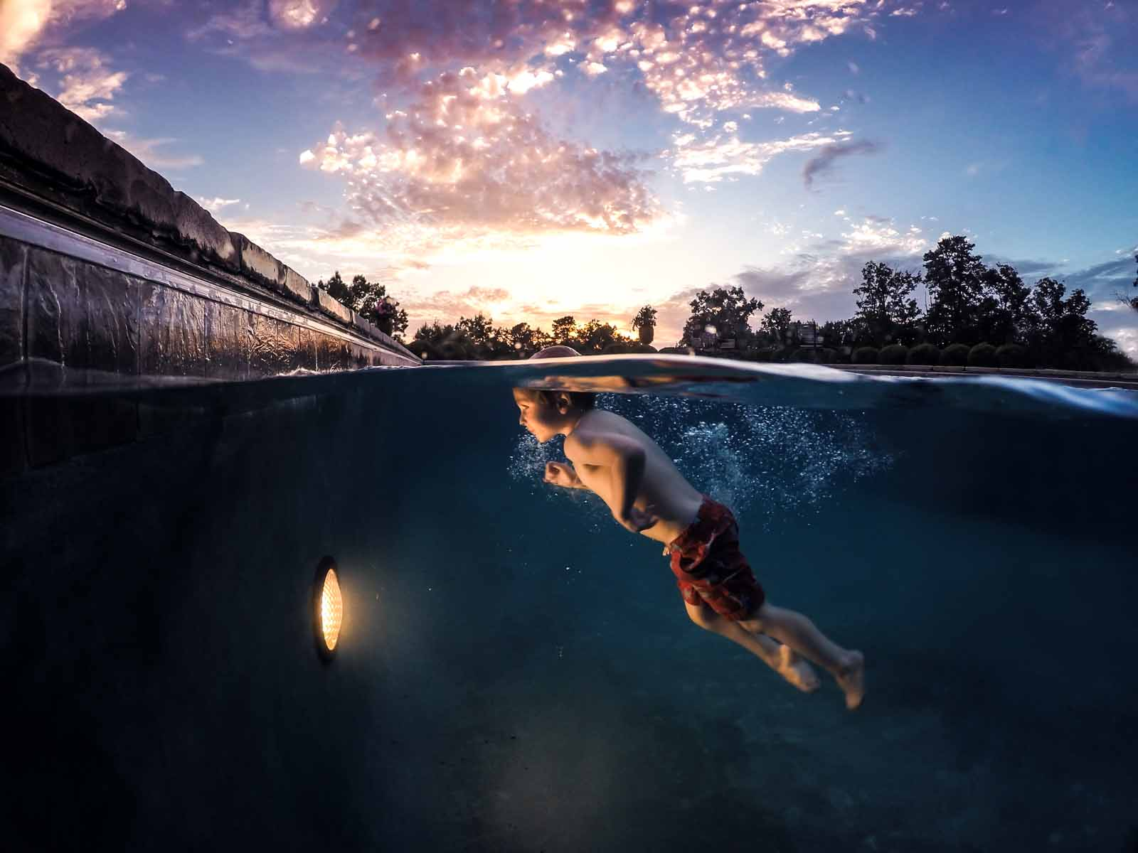 Night photography underwater image of boy swimming in pool