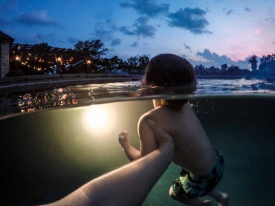 Mom holds a little boy swimming at night in an underwater photo
