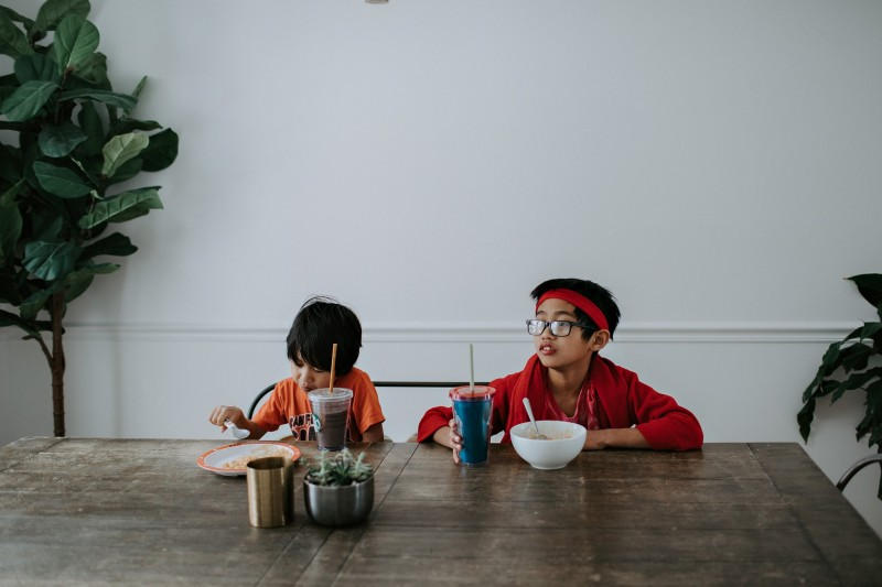 Two boys eat at a dining room table by Winnie Bruce