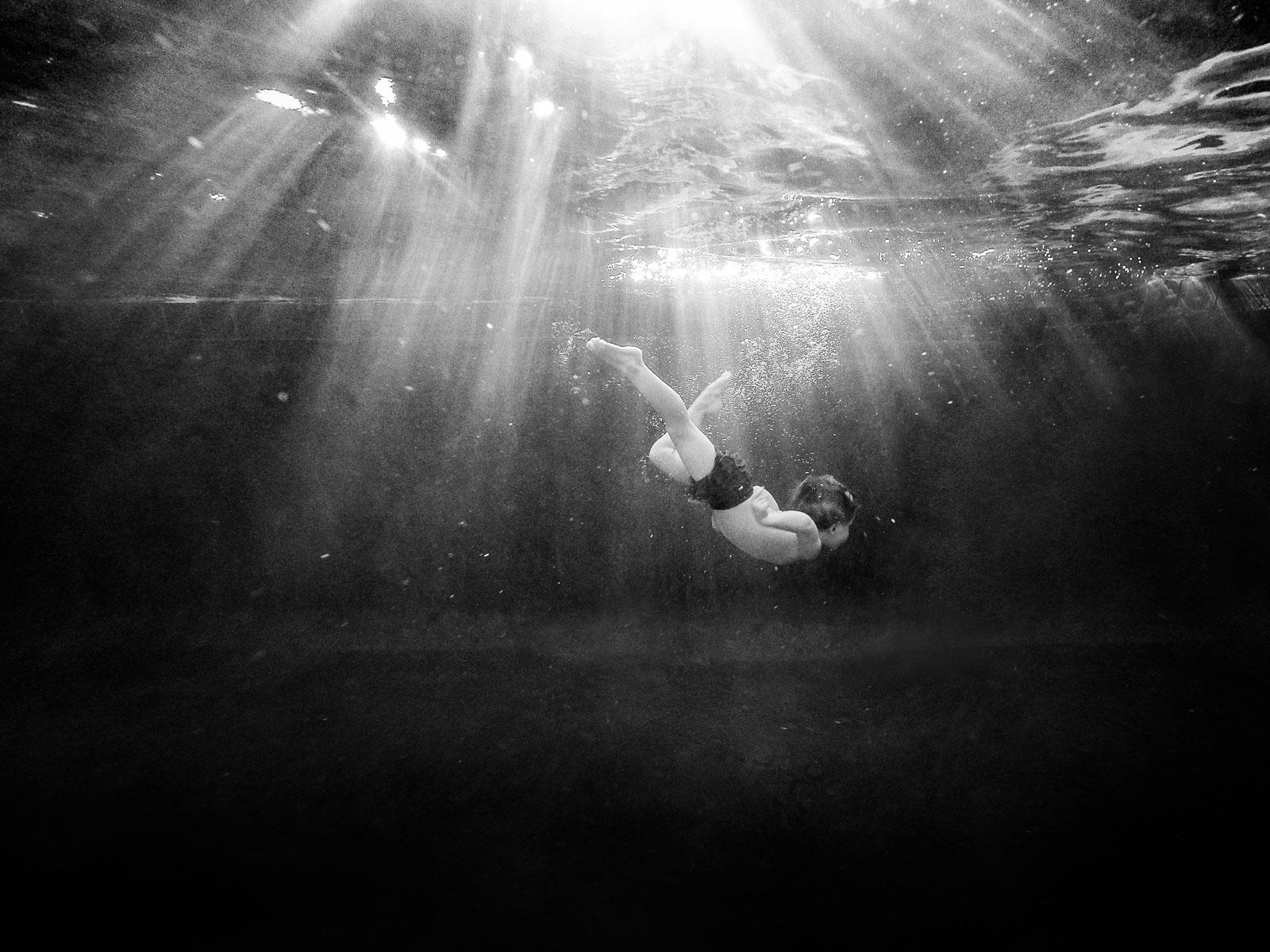 Underwater photo of boy swimming in rays of light