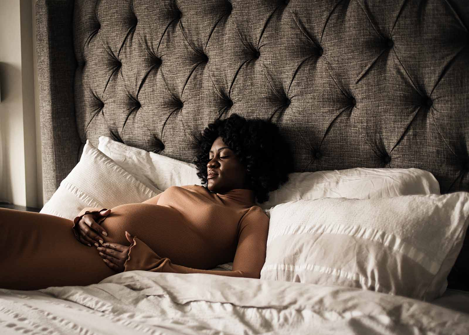 Maternity photo of woman on a bed in moody light