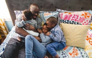 A dad snuggling his three children. Photo by Lucy Baber.