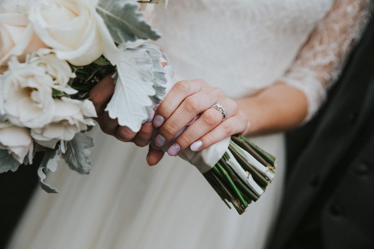 A human element to photographing details is a hand holding a bouquet.