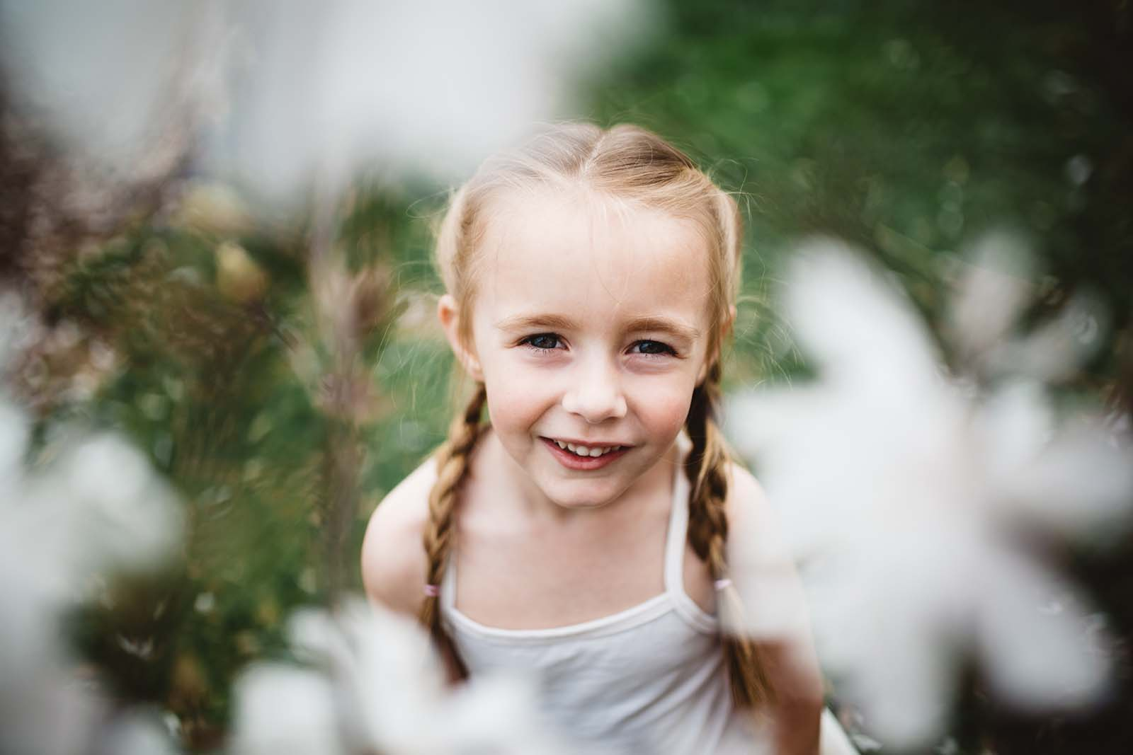 A smiling girl through flowers. Finding balance with photography and motherhood