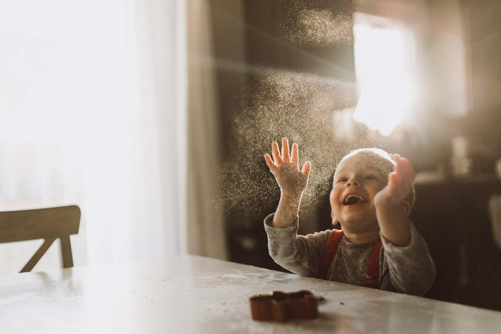 A joyful boy through a window. Finding balance with photography and motherhood
