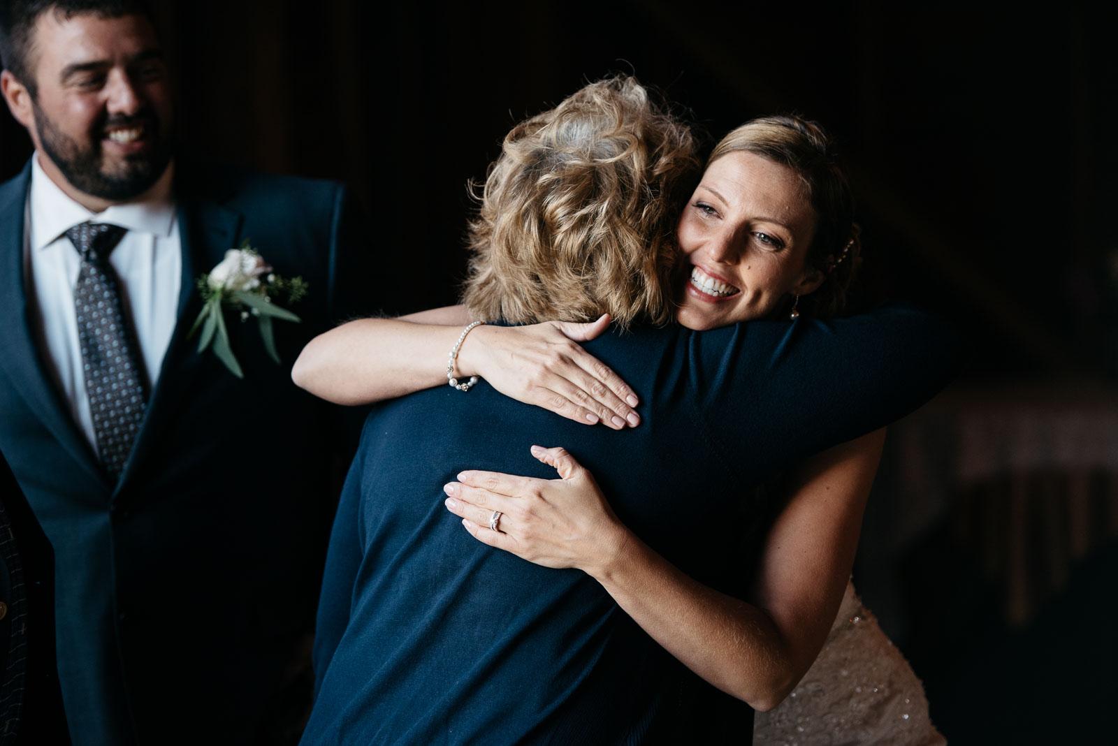 A mom hugs a bride at a wedding