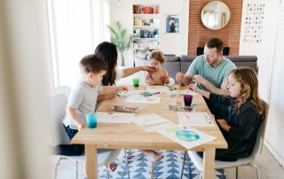 A family draws at a table day in the life session of photography