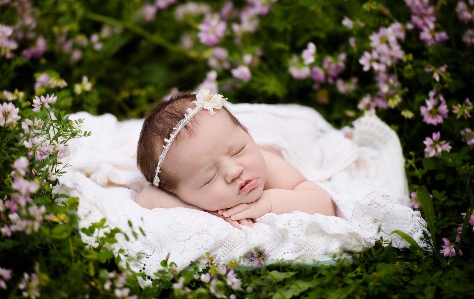 Adorable newborn baby girl surrounded by flowers