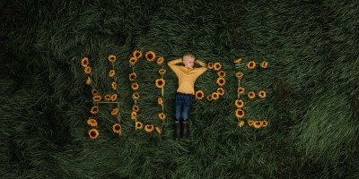 Boy laying on word Hope spelled in gold flowers
