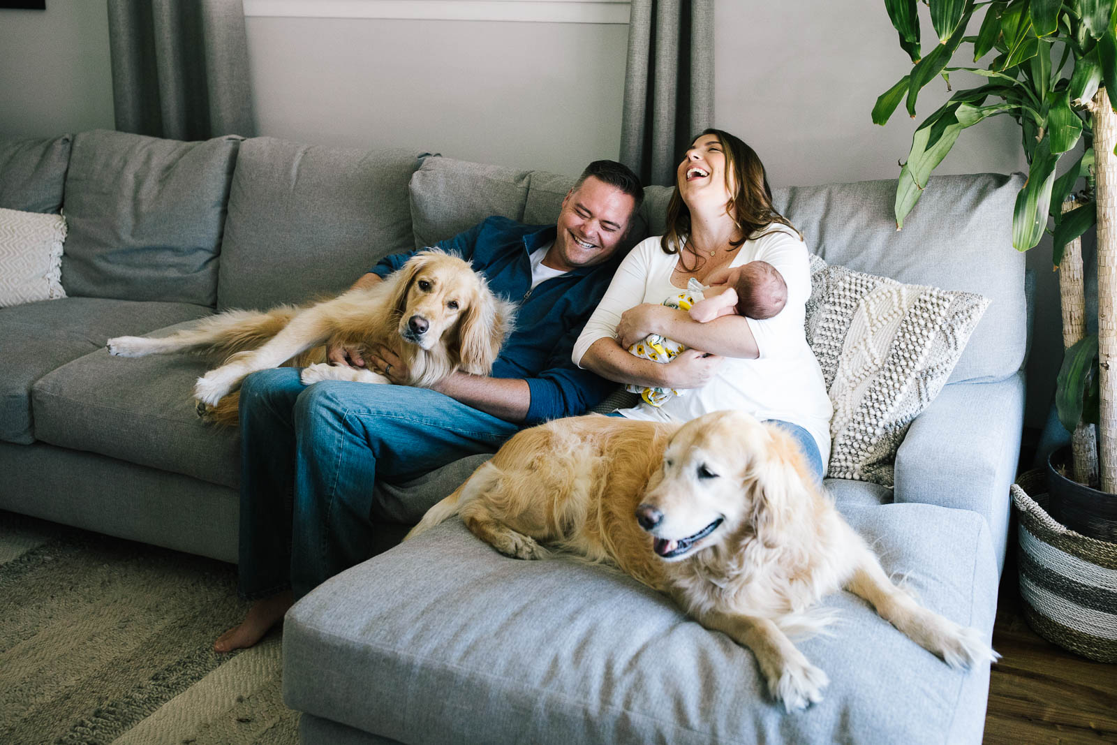 A family laughs on the sofa with their two dogs and newborn baby - How to get natural smiles in photos.