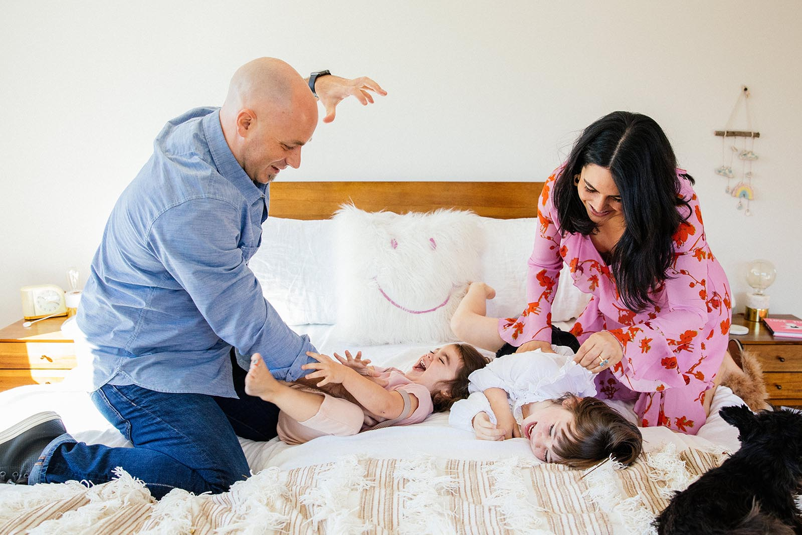 A family plays on a bed