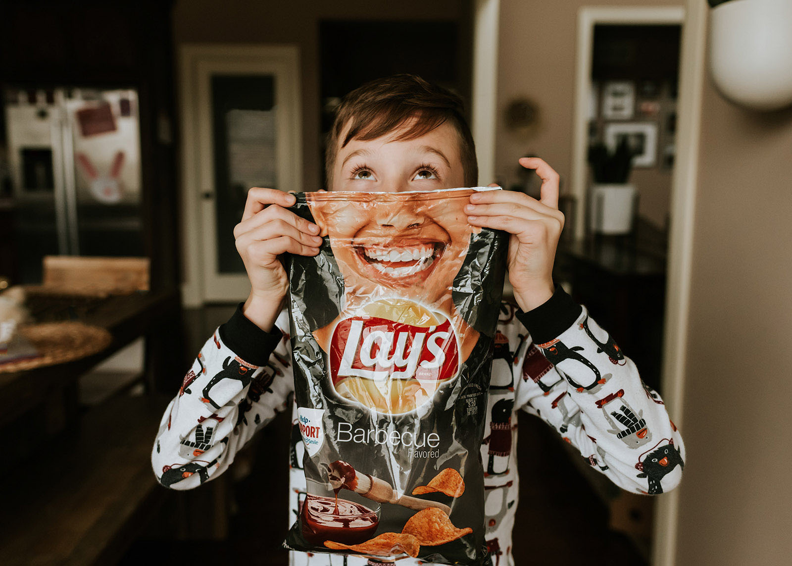 A boy holds up a bag of potato chips with a smile for a hilarious image