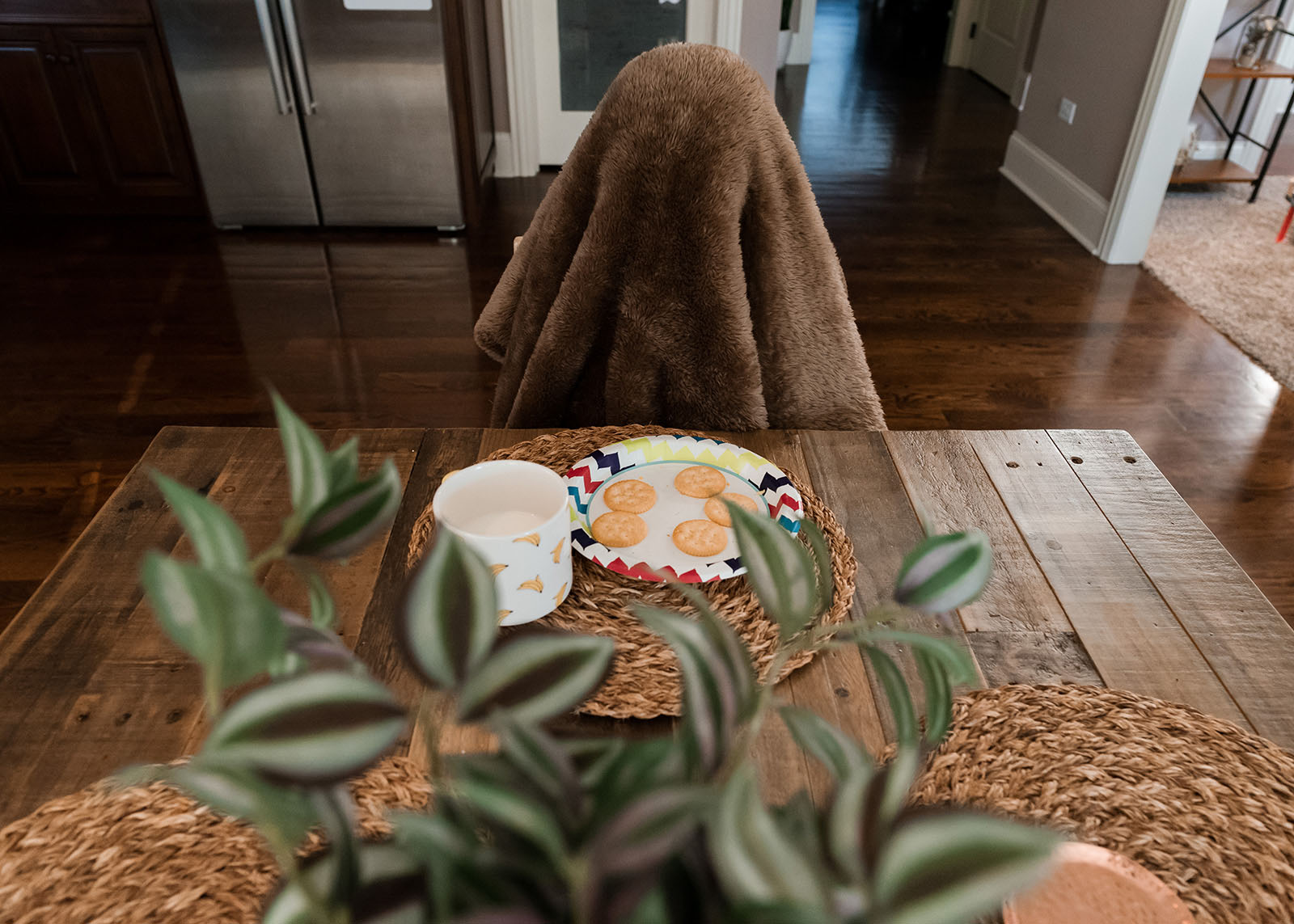 A child sits at the table with a blanket over his head in this funny everyday image.