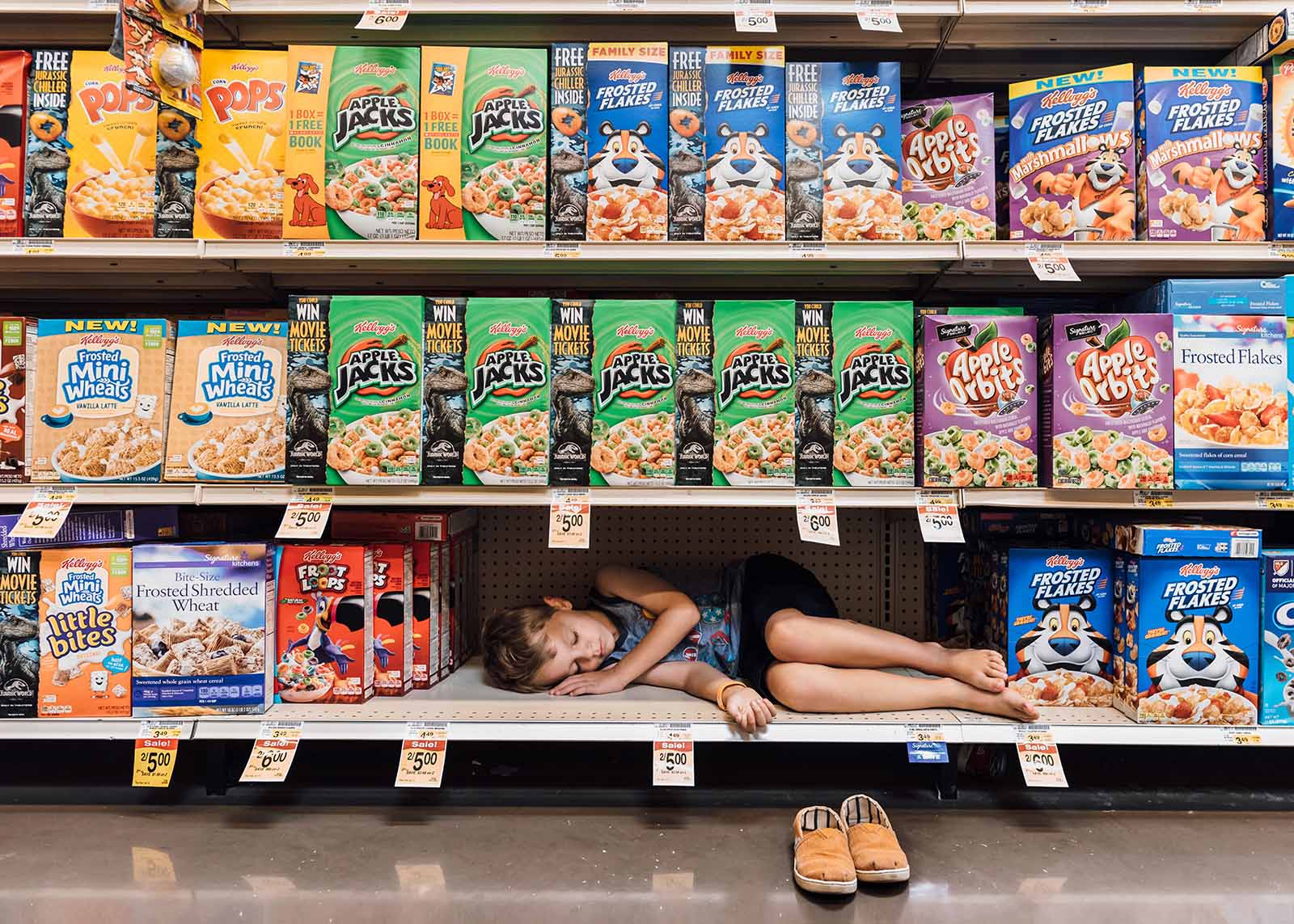 A boy naps on a supermarket shelf next to the cereal.