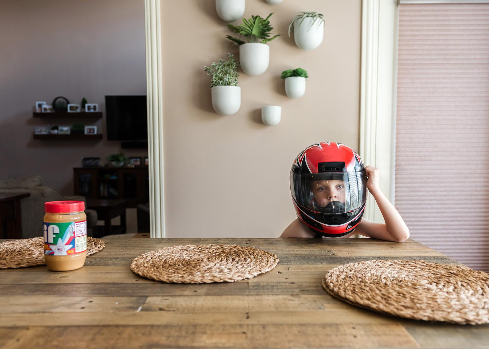 A boy sits at the table wearing a motorcycle helmet in this humorous everyday image.