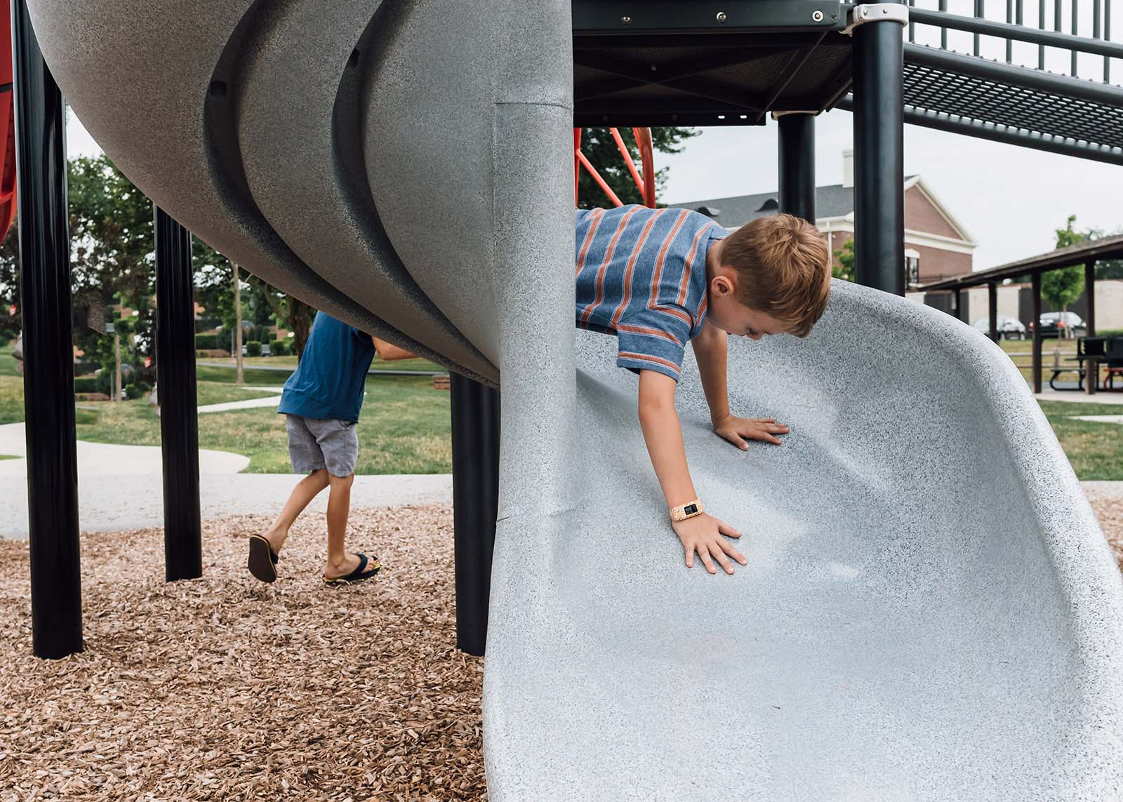 A boy slides down a curved slide while another runs under, creating a humorous image.