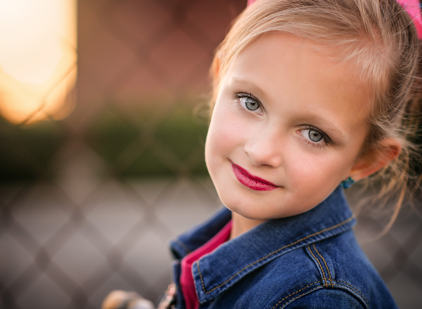 A little girl wearing lipstick poses for a photo