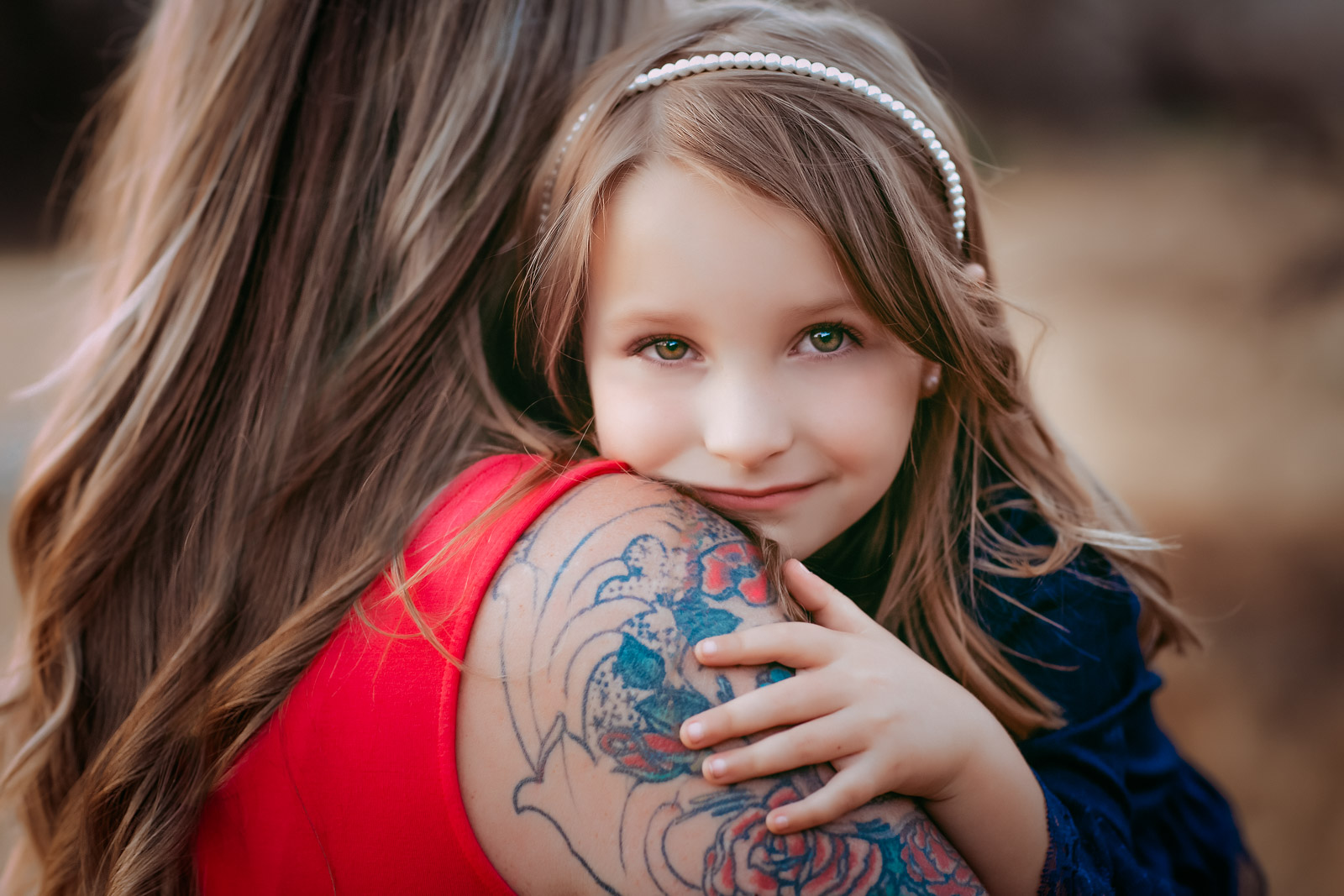 A little girl with special needs rests her chin on mom's shoulder