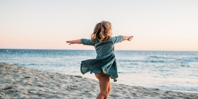 How to photograph special needs children - A girl twirls on the beach.
