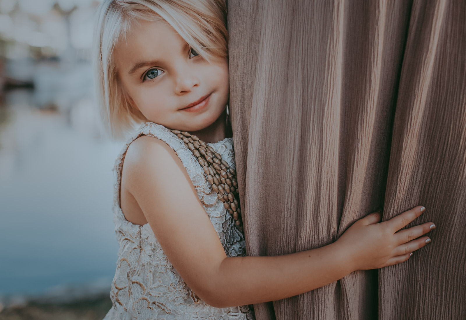 A little girl peeks from behind mom's legs - How to photograph special needs children and their families